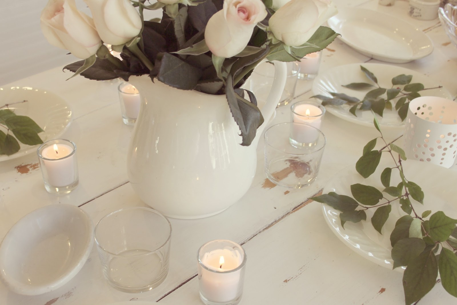 White farmhouse table with pink roses, candlelight, and greenery by Hello Lovely Studio