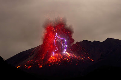 A black volcano erupting in red lava with a purple electrical charge.Photo by Marc Szeglat.