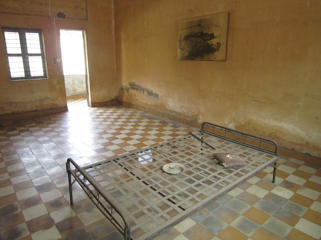 Una de las habitaciones de tortura del S-21 con foto en la pared de un hombre muerto por tortura