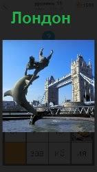 Знаменитый Лондонский мост  и из воды выскочили дельфин и человек держащий его за плавники