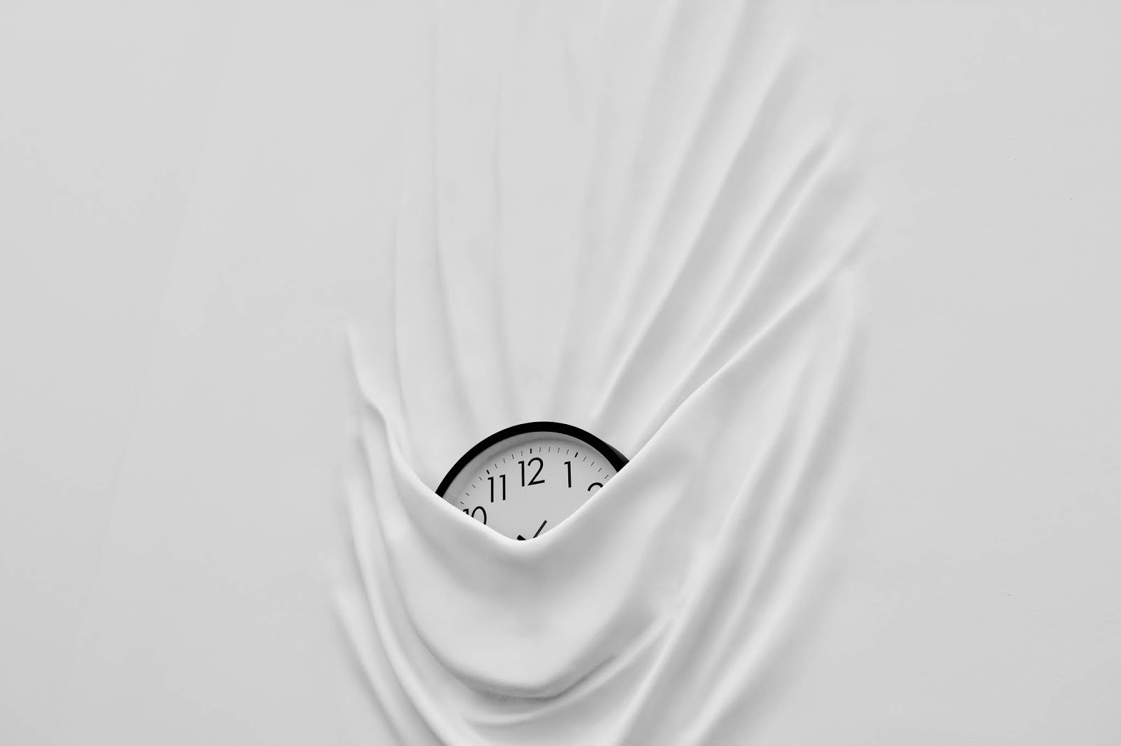 An image of a clock sinking into a wall, which was taken at the Moco Museum in Amsterdam