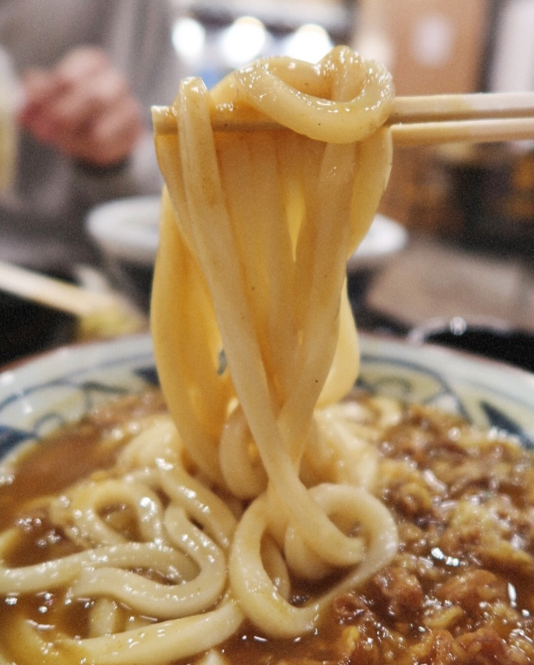 A close up shot of Marugame Udon's curry noodle udon bowl with al dente-style noodles.