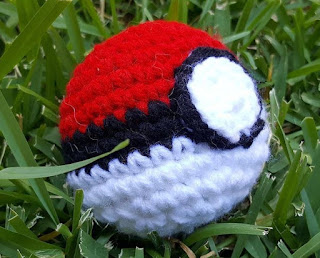 Nestled in grass, a red, black and white knitted ball, decorated to resemble the Pokemon Go 'Pokeball'