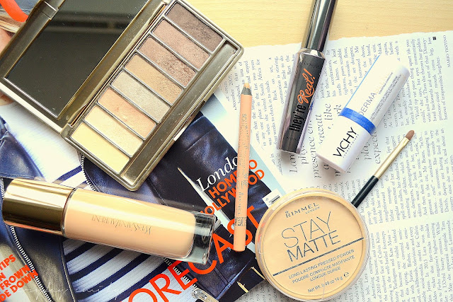 A flat lay of makeup prodcuts including; YSL le teint touche eclat, rimmel stay matte powder, rimmel scandaleyes liner in nude, benefit they're real mascara, no7 stay perfect eyeshadow palette, vichy dermablend concealer