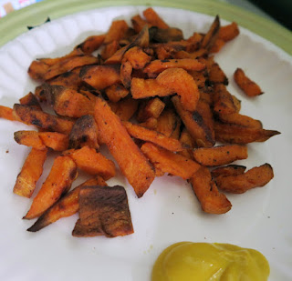 Baked sweet potato fries with mustard on the side, on a paper plate.