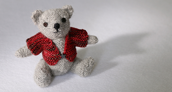 Hand Knit Light Gray Wool Teddy Bear in a Red Sweater on a White Background