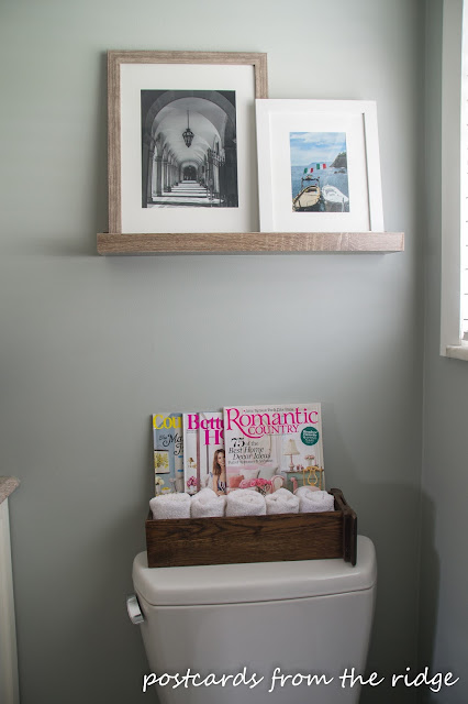 Picture ledge with personal photos and an old sewing drawer behing the toilet. Postcards from the Ridge.