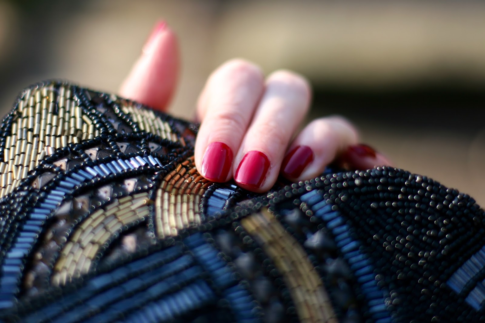 Red nails and a beaded clutch bag.