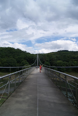 Blick auf die Brücke. Am Ende steht ein hoher Mast, der die Brückenkabel hält