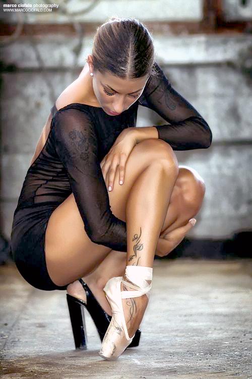 Una bailarina de ballet en cuclillas, lleva un tatuaje en la pantorrilla , el tatuaje es de una bailarina de ballet