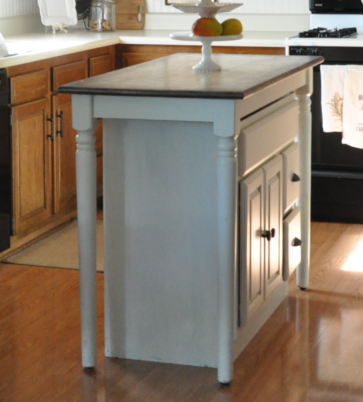 building kitchen island make kitchen table Paint a high table with a base cabient to make it look like a cohesive cabinet