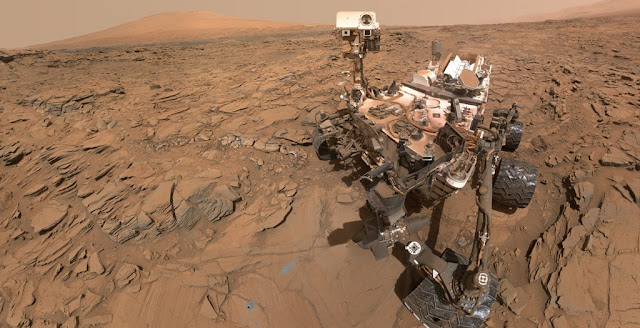 "This May 11, 2016, self-portrait of NASA's Curiosity Mars rover shows the vehicle at the ""Okoruso"" drilling site on lower Mount Sharp's ""Naukluft Plateau."" The scene is a mosaic of multiple images taken with the arm-mounted Mars Hands Lens Imager (MAHLI). Credit: NASA/JPL-Caltech/MSSS"