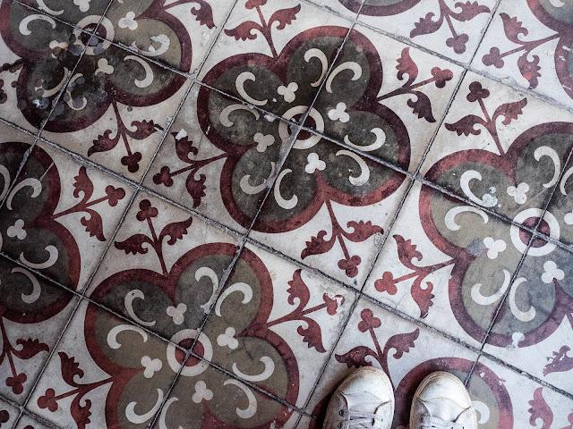 Detalle de un suelo de baldosas hidráulicas en tonos rojo, gris y blanco