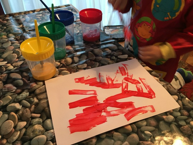 Painting-and-Playgrounds-paint-pots-and-toddler-painting-red-on-white-paper