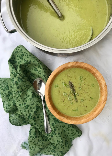 A large pot of creamy asparagus soup along with a bowl filled with soup.