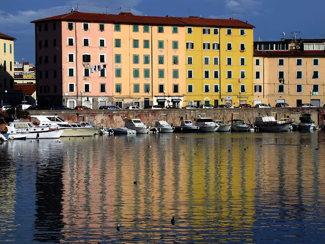 Pastel colored buildings reflected in water, Scali delle Cantine, Livorno