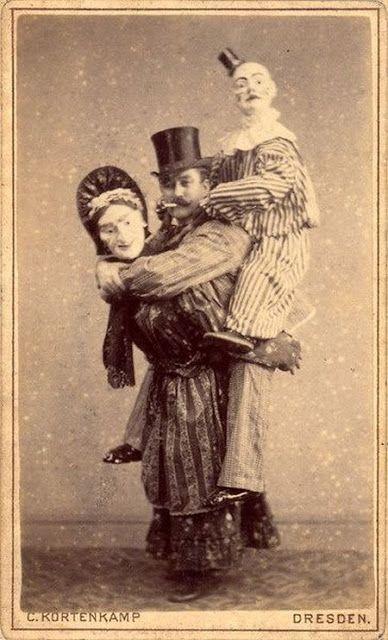 Hombre a lomos de una muñeca cargando con un payaso