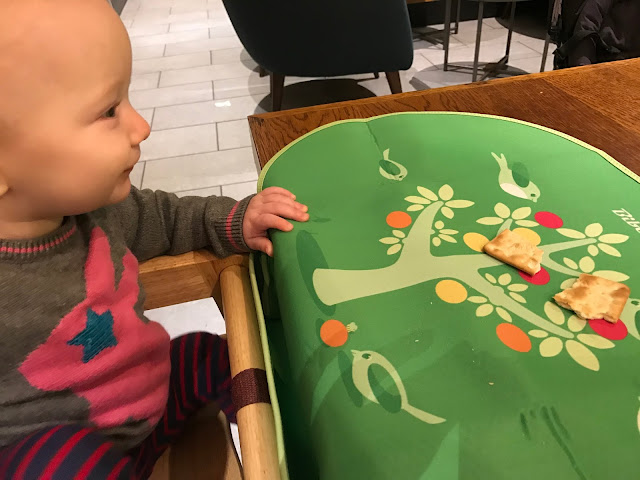 A baby with a pink rabbit on her grey jumper sitting in a highchair in Starbucks. A green Bibetta placemat is on the table in front