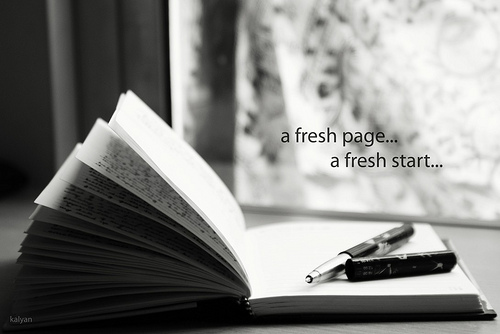black and white photograph of a book with text on top of it saying a fresh page a fresh start