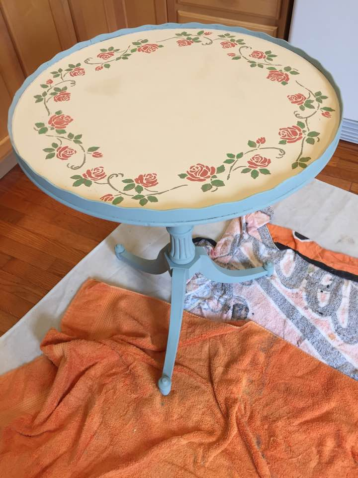 Pedestal table with stenciled border.