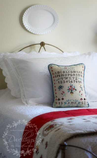 Sampler pillow and red antique quilt in the guest room