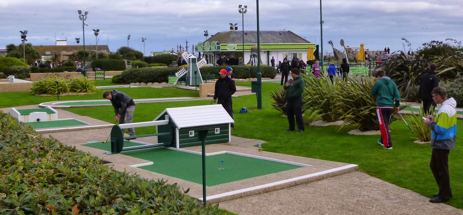 2014 World Crazy Golf Champion Chris 'Who' Harding on his way to victory in the final round of the tournament played at Hastings Sea Front. Opponents Nuno Cunha (POR) and Adam Kelly (ENG) look on, as do referee John McIver and scorekeeper Adrian Amey