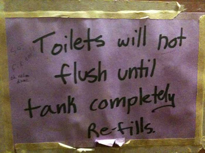 Purple construction paper sign with black marker lettering explaining that the toilet tank needs to refill before it can be flushed again