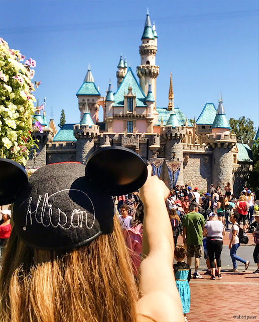 Pointing at Sleeping Beauty's castle wearing Mickey Mouse Ears with the name Allison on the back