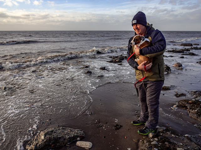 Photo of Phil holding Ruby after she asked to be picked up when a wave almost reached her