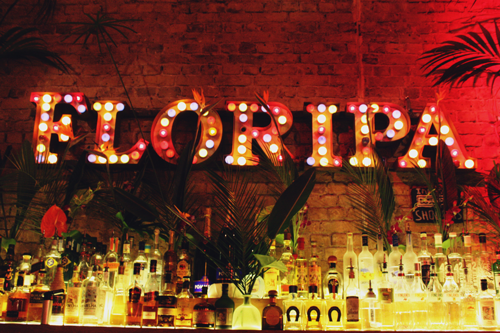 the floripa logo written out in lightbulbs behind a bar stocked with hundreds of glass bottles