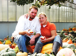 a man and woman sitting on a large pile of different kinds of pumpkins and squash