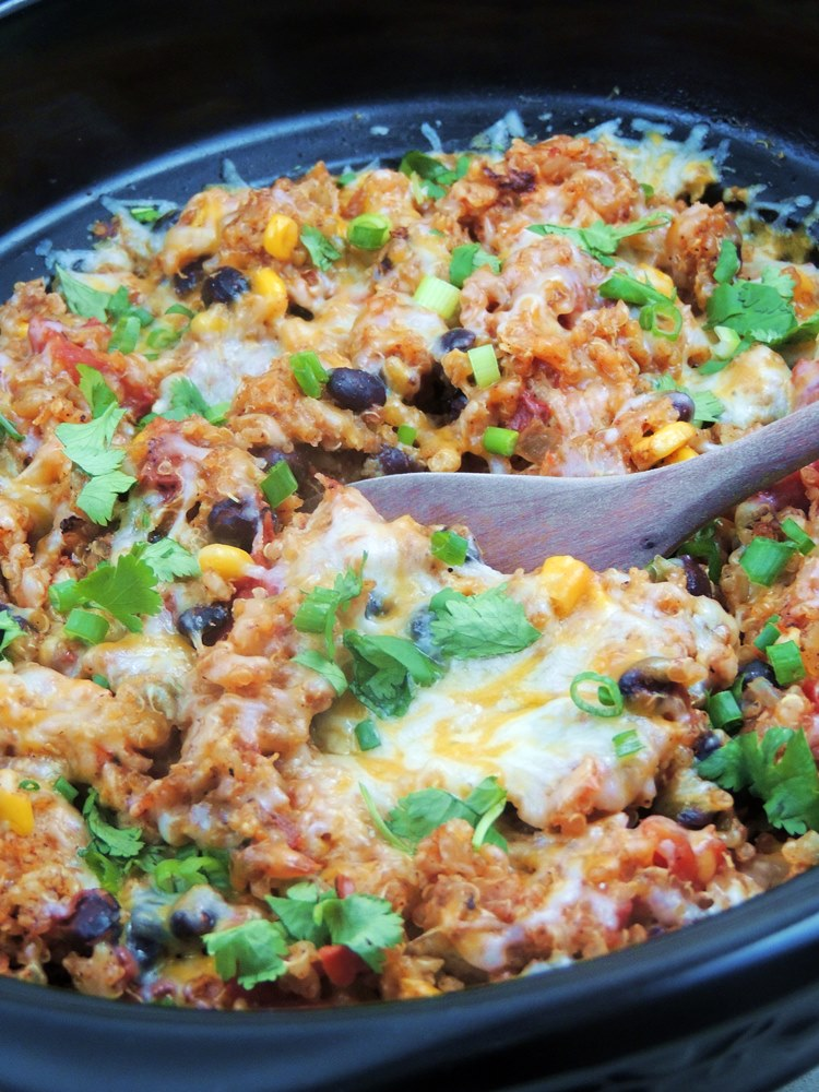 Slow Cooker Chicken Enchilada Quinoa in the crockpot with a spoon.