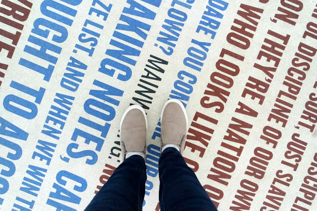 my feet on a white floor with red and blue words on it