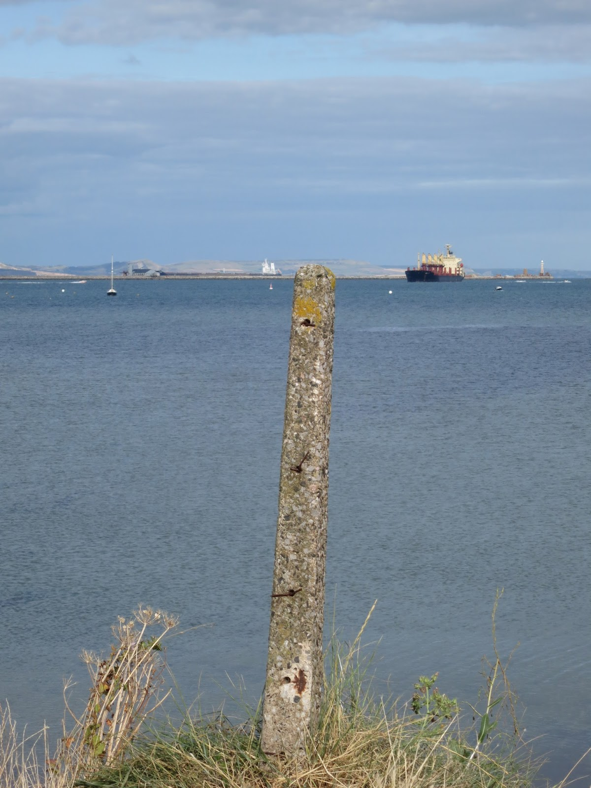 Lopsided concrete post in front of sea with ship and distant hills
