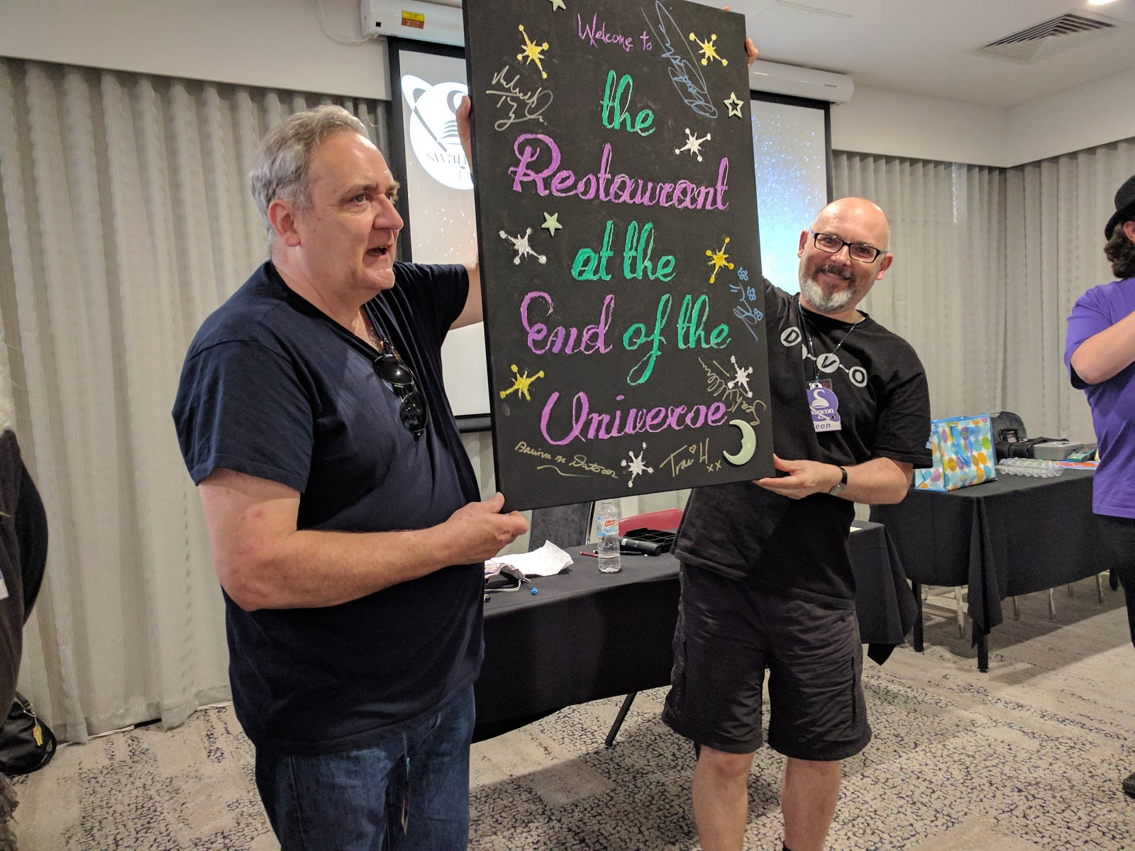 (michael Troughton And Sean Williams Holding Up The Swancon Costume Party  Sign)