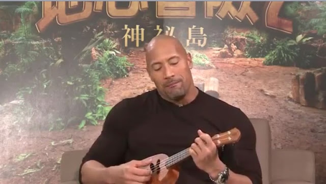 The Rock playing ukulele