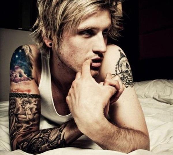 Chico rubio en la cama lleva tatuajes den el brazo
