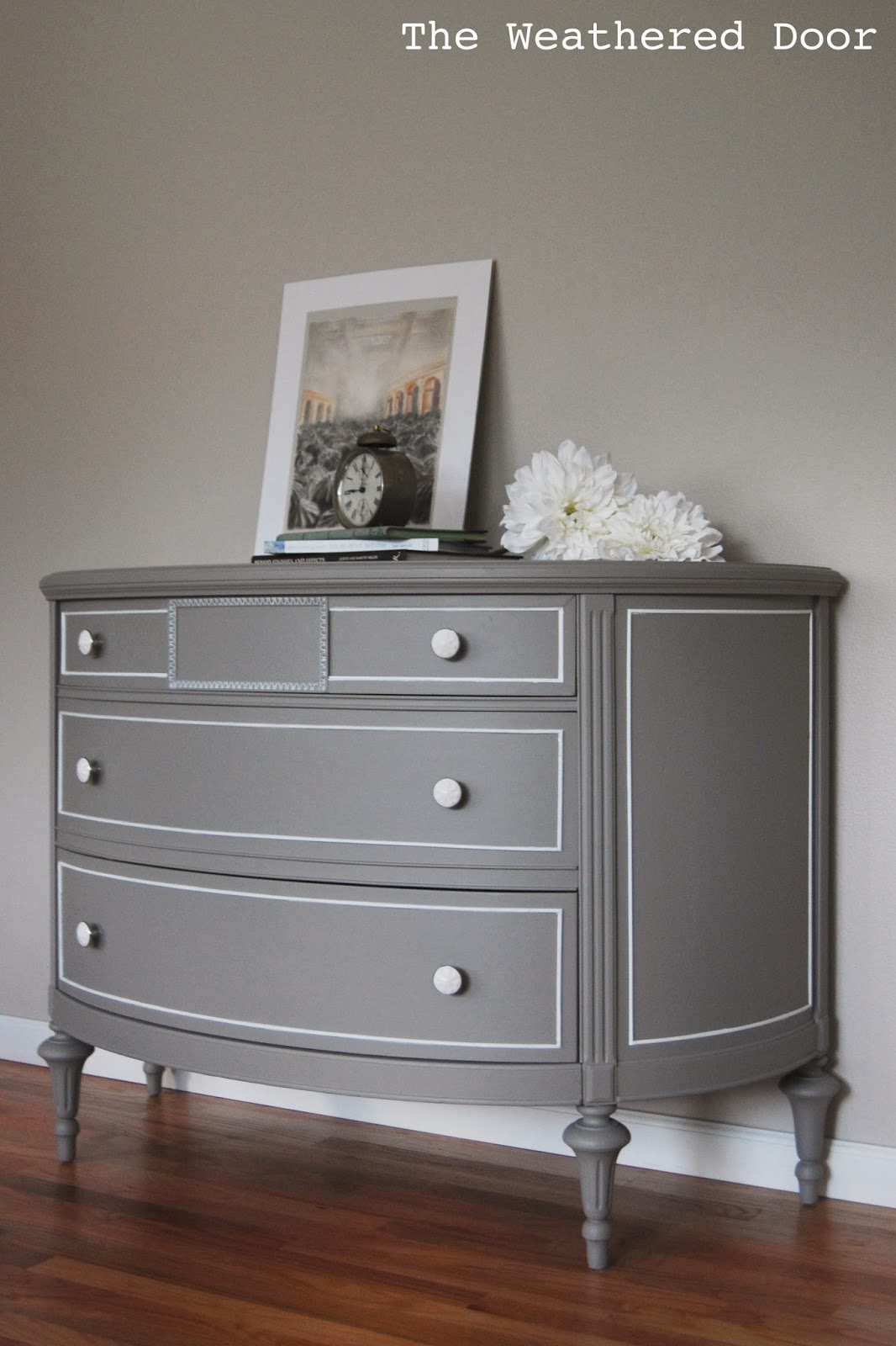 a grey demi lune dresser with white accents  the