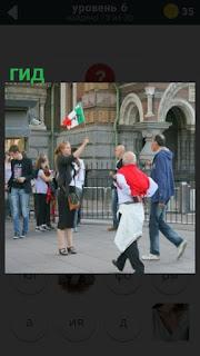 стоит женщина гид с флагом и предлагает экскурсию