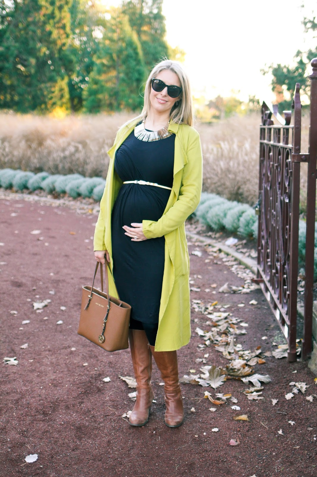 The Goldfields Girl styling maternity fashion. She wears black maternity dress, green jacket, statement gold necklace, brown boots and Michael Kors bag.