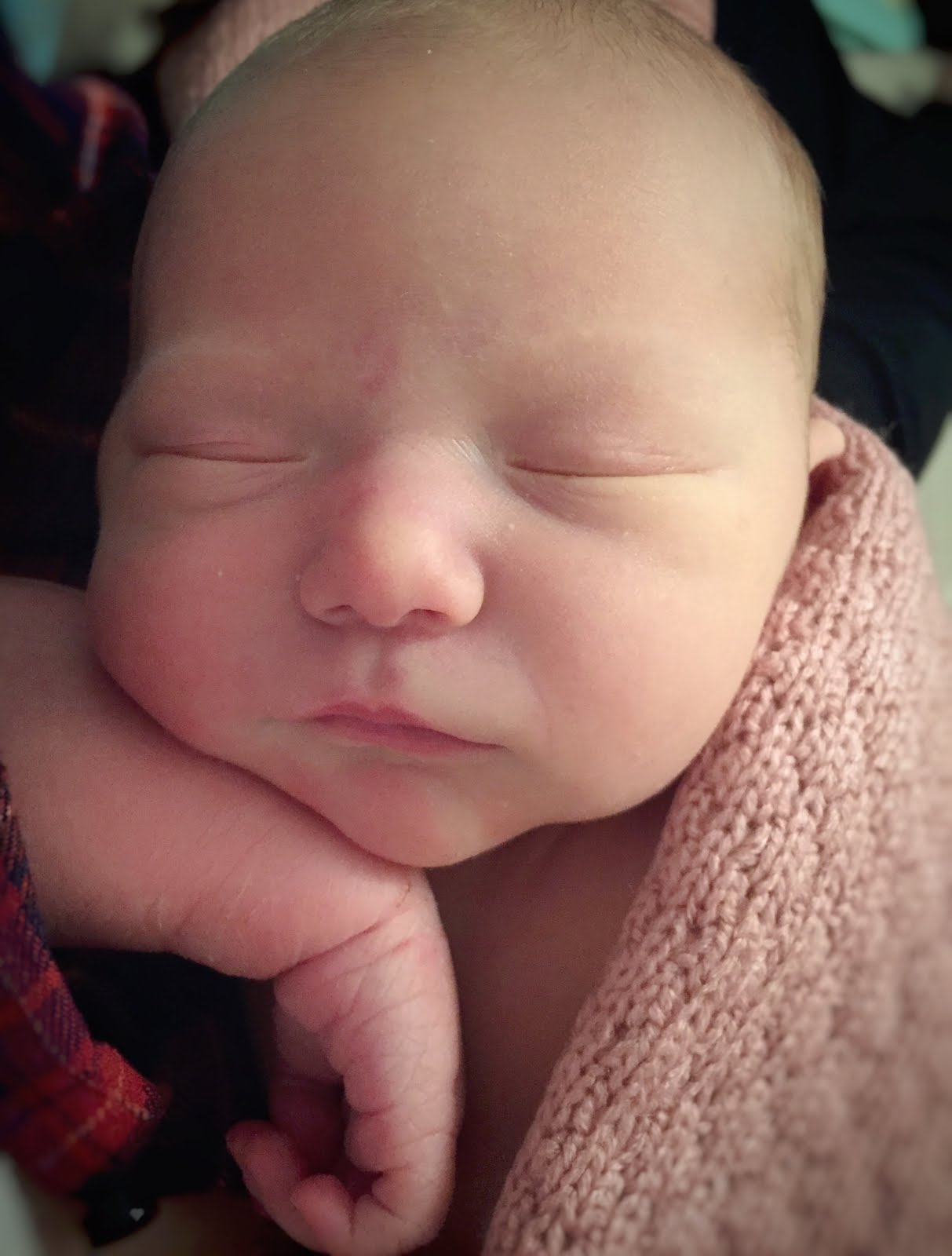 A close up of a newborn baby with her eyes closed resting on her arm