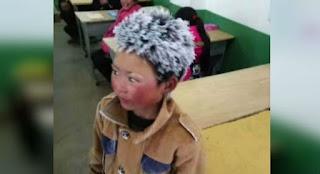 """Um menino chinês ficou conhecido na web como """"frost boy"""" (menino congelado) depois que uma foto dele mostrando seus cabelos cobertos por gelo viralizou nas redes sociais. A imagem abriu espaço para um debate sobre a pobreza na China, diante das condições de vida pelas quais passam as crianças que vivem nas áreas rurais. O pequeno Wang Fuman ficou naquele estado após andar por quatro kilometros e meio para chegar à escola primária onde estuda, no sudoeste da província de Yunnan, enfrentando os 9 graus negativos que fazia.  A foto mostra Yunnan da cintura para cima, cabelos brancos de puro gelo, bem como as sobrancelhas e as pestanas, e as bochechas bem vermelhas; usa um casaco marrom de botoes redondos e com as pontas da gola para cima. Yunnan observa a esquerda."""