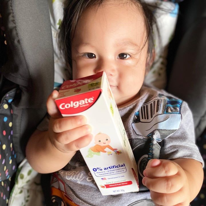 Baby holding a Colgate kiddie toothpaste to instill the habit of good oral hygiene