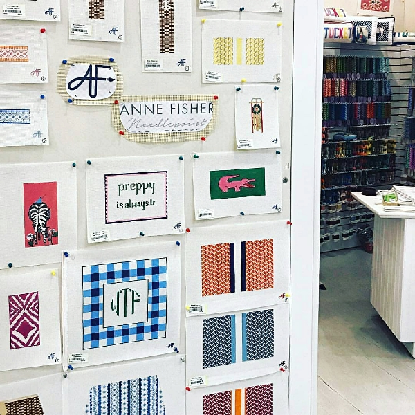Anne Fisher's needlepoint canvases on a wall display in a sewing shop
