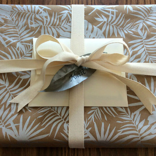 rectangular present wrapped in silver leafy silk-screened kraft paper with ribbon, card, envelope and personalized painted silver leaf