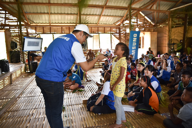 Children from Kampung Ulu Tual happily engaging with Samsung volunteers during the pop quiz session