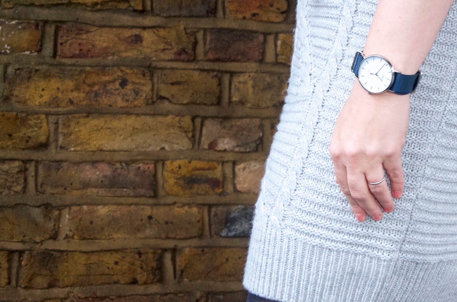 navy & silver timex watch, gray knit dress and brick wall