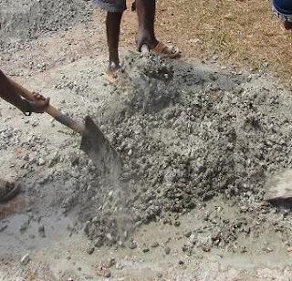 Dry mixing of cement and all aggregate before sprinkling of water in hand mixing of concrete