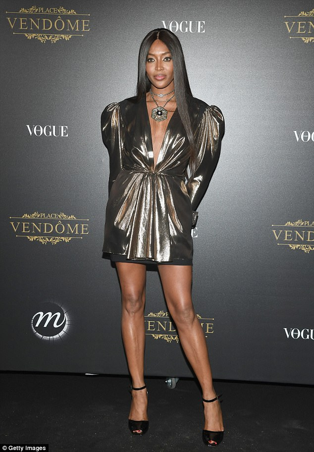 Naomi Campbell flaunts her long pins in short gold dress for Vogue Party