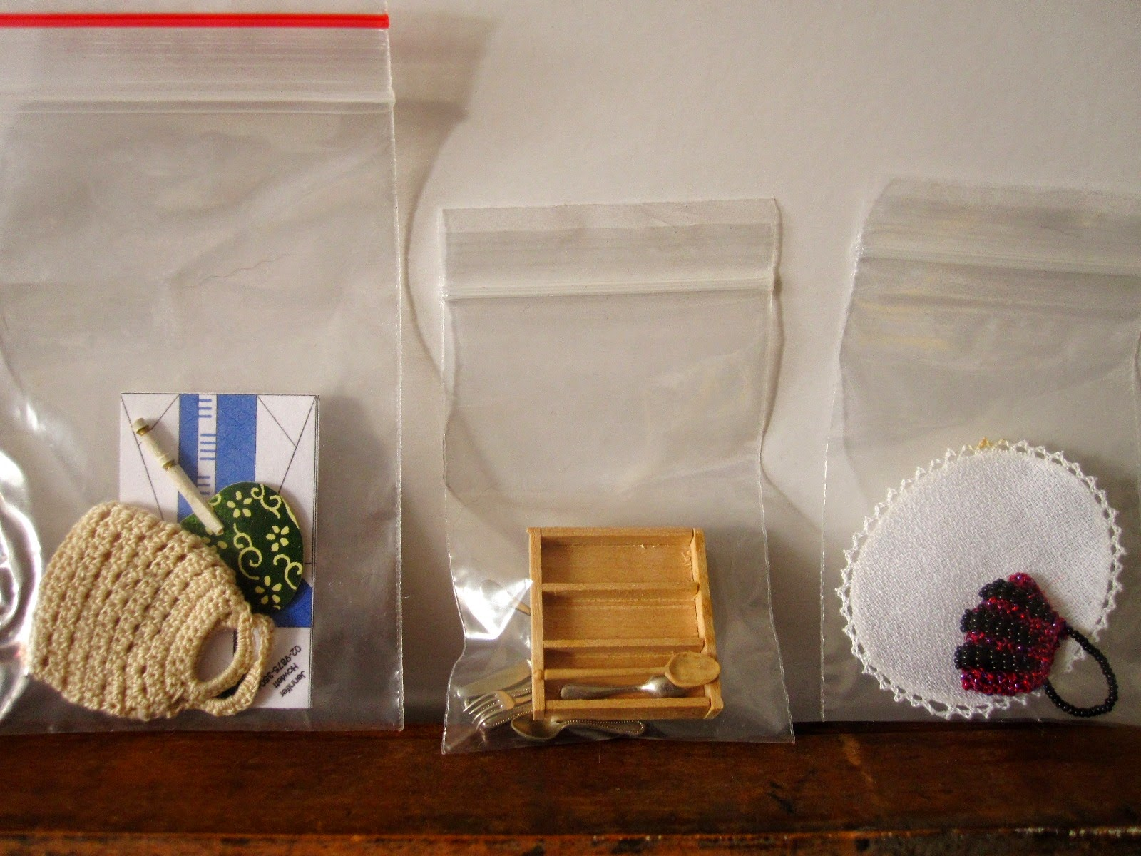 Three bags of miniature dolls' house accessories including a crocheted shopping bag, a cutlery tray and a tray cloth with crocheted edge.